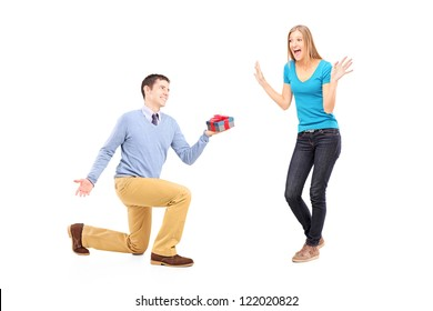 Full length portrait of a male on knee giving a gift to his excited girlfriend isolated on white background