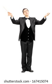 Full length portrait of a male orchestra conductor directing with baton isolated on white background