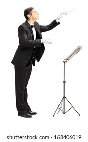 Full length portrait of a male orchestra conductor directing with stick isolated against white background