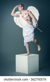 Full length portrait of a man angel Cupid posing like a statue. Valentine's day. Love concept.