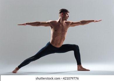 Full length portrait of a man doing yoga exercises isolated on a white background