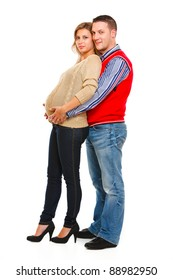 Full length portrait of man hugging her pregnant wife isolated on white