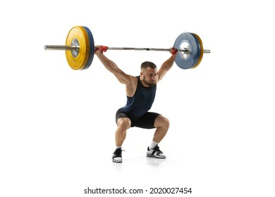 Full length portrait of man in sportswear exercising with a weight isolated on white background. Fit young muscular caucasian model with barbell training at abstract gym. Sport, weightlifting concept