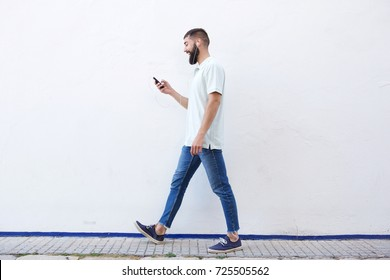Full length portrait of man walking and holding mobile phone with headphones