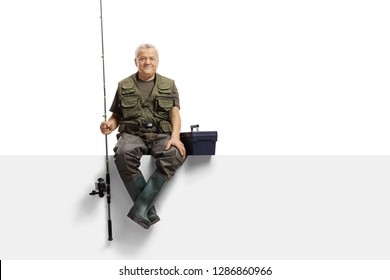 Full length portrait of a mature fisherman with a fishing rod sitting on a panel isolated on white background