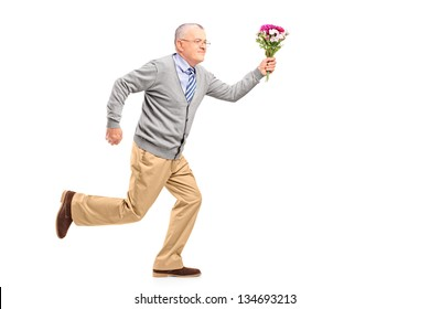 Full length portrait of a mature gentleman running with flowers, isolated on white background