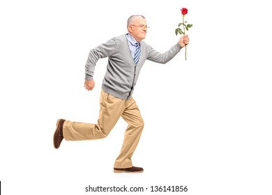 Full length portrait of a mature gentleman running with a red rose, isolated on white background