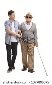 Full length portrait of a mature man walking with the help of a young guy isolated on white background