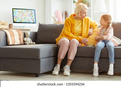 Full length portrait of mature woman building house while playing with little girl at home, copy space