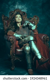 Full length portrait of a medieval queen in knightly armor sitting on a throne on a vintage background. History of the Middle Ages.
