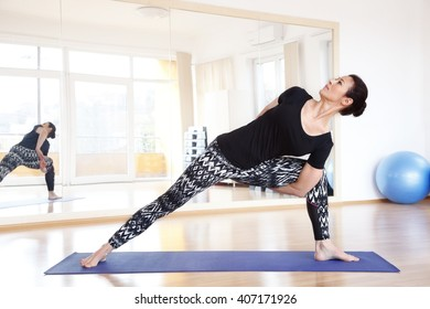 Full length portrait of a middle age woman doing yoga on an exercise mat at yoga studio.