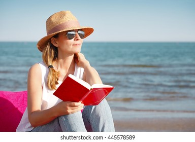 Full length portrait of middle age woman reading book on the beach. Beautiful female wearing casual clothes and straw hat during on her summer vacation.