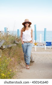 Full length portrait of middle aged woman leisurely walking on the beach while on summer vacation.
