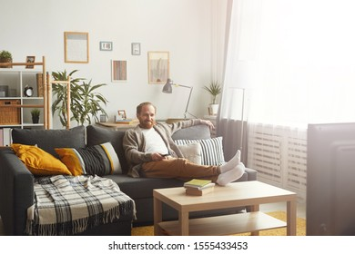 Full length portrait of modern adult man relaxing on couch while watching TV at home, copy space