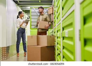 Full length portrait of modern couple using digital tablet while loading boxes into self storage container, copy space