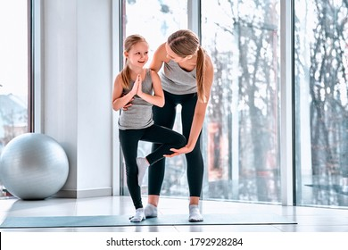 Full length portrait of mother gently teaching little daughter her first yoga notions careful near kids body helping daughter finished action in the fitness class at school.