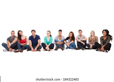 Full length portrait of multiethnic college students sitting in a row against white background