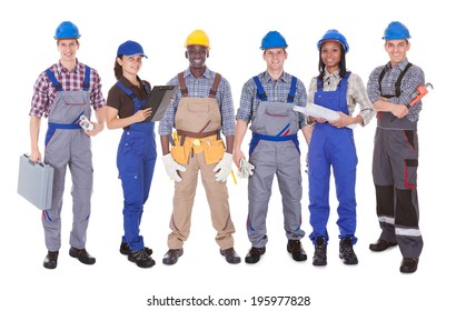 Full length portrait of multiethnic engineers standing against white background