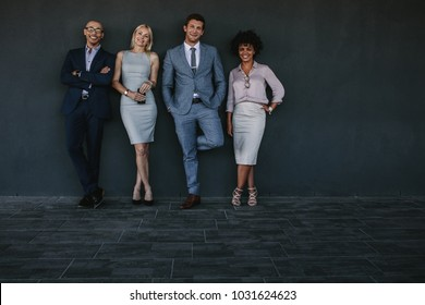 Full length portrait of multiracial team of business professionals standing together. Team of corporate business professionals against a wall.