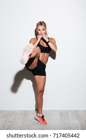 Full length portrait of muscular concentrated sportswoman doing kickboxing exercises and looking at camera isolated over white background