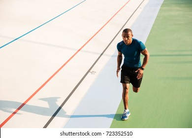 Full length portrait of a muscular sportsman running on a track field outdoors