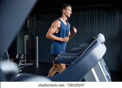 Full length portrait of muscular sportsman listening to music in headphones and using treadmill while wrapped up in training at modern gym, profile view