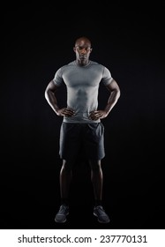 Full length portrait of muscular young man in sportswear looking at camera against black background. Strong african athlete with his hands on hips.