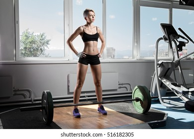 Full length portrait of muscular young woman standing at gym with barbells on floor. Strong female at gym.