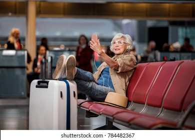 Full length portrait of old lady is sitting on bench at airport lounge. She is having video call using smartphone and earphones while putting legs on suitcase and looking at screen of gadget
