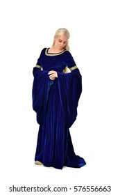 Full length portrait on a beautiful young woman with long blonde hair, wearing a blue velvet medieval gown. standing pose, isolated on white background.