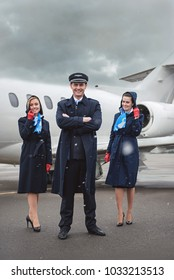 Full length portrait of outgoing pilot and beaming air-hostesses locating opposite aircraft at airfield. Profession concept