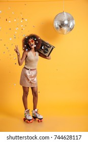 Full length portrait of overjoyed afro american disco woman in sunglasses showing peace gesture, standing on roller skates, holding boombox, looking at camera, isolated on yellow background