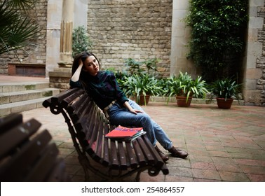 Full length portrait of pensive brunette hair woman sitting in beautiful spanish patio bench propping up her head with hands and look to the camera