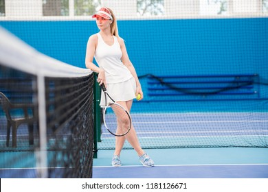 Full length portrait of pensive young woman standing on tennis court leaning on net, copy space