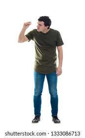 Full length portrait perplexed young man holding something tiny between his fingers, looking confused isolated over white background. Showing a small object between thumb and forefinger.