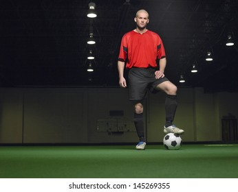 Full length portrait of a player with leg on football
