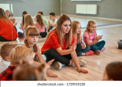 Full length portrait of a postive young dance teacher talking to group of little happy girls and boys sitting on the floor in the dance studio. Relationship between teacher and kids