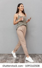 Full length portrait of a pretty asian woman holding takeaway coffee cup and using mobile phone while walking isolated over gray background