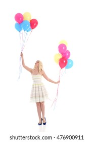 Full length portrait of a pretty blonde girl wearing a white dress, holding a bunch of colourful balloons. Isolated on what background.