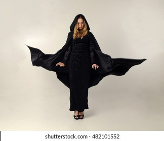 full length portrait of a pretty blonde lady wearing a gothic black dress and hooded cloak. standing pose against a grey background.