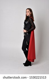 full length portrait of a pretty brunette woman wearing black leather fantasy costume with long red superhero cape. standing pose on a studio background.