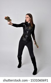 full length portrait of a pretty brunette woman wearing black leather fantasy costume with a gun. standing pose on a studio background.