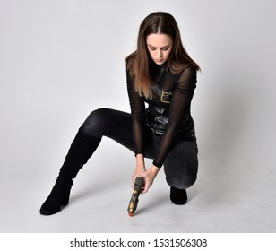 full length portrait of a pretty brunette woman wearing black leather fantasy costume. Crouching pose on a studio background.