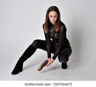 full length portrait of a pretty brunette woman wearing black leather fantasy costume. Sitting down with  a studio background.