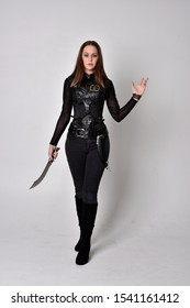 full length portrait of a pretty brunette woman wearing black leather fantasy costume