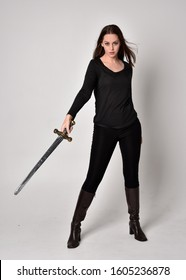 full length portrait of a pretty brunette girl wearing a black shirt and leather boots, holding a sword. Standing pose, holding a sword, on a grey studio background.