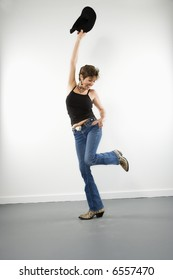 Full length portrait of pretty Caucasian woman holding up cowboy hat in playful pose.