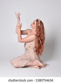 full length portrait of a pretty, fairy girl wearing a nude flowy dress and crystal crown. Sitting pose against a grey studio background.