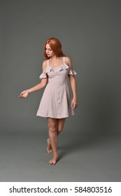 full length portrait of a pretty girl with long copper hair, wearing a simple purple dress. standing against a grey background.