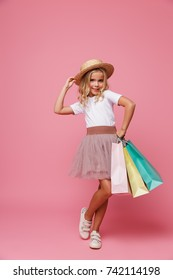 Full length portrait of a pretty little girl in hat and skirt holding shopping bags while standing isolated over pink background